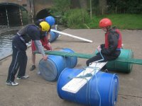 The team builds the bridge by using barrels, ropes and planks