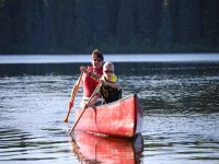 man and child paddle a sport canoe
